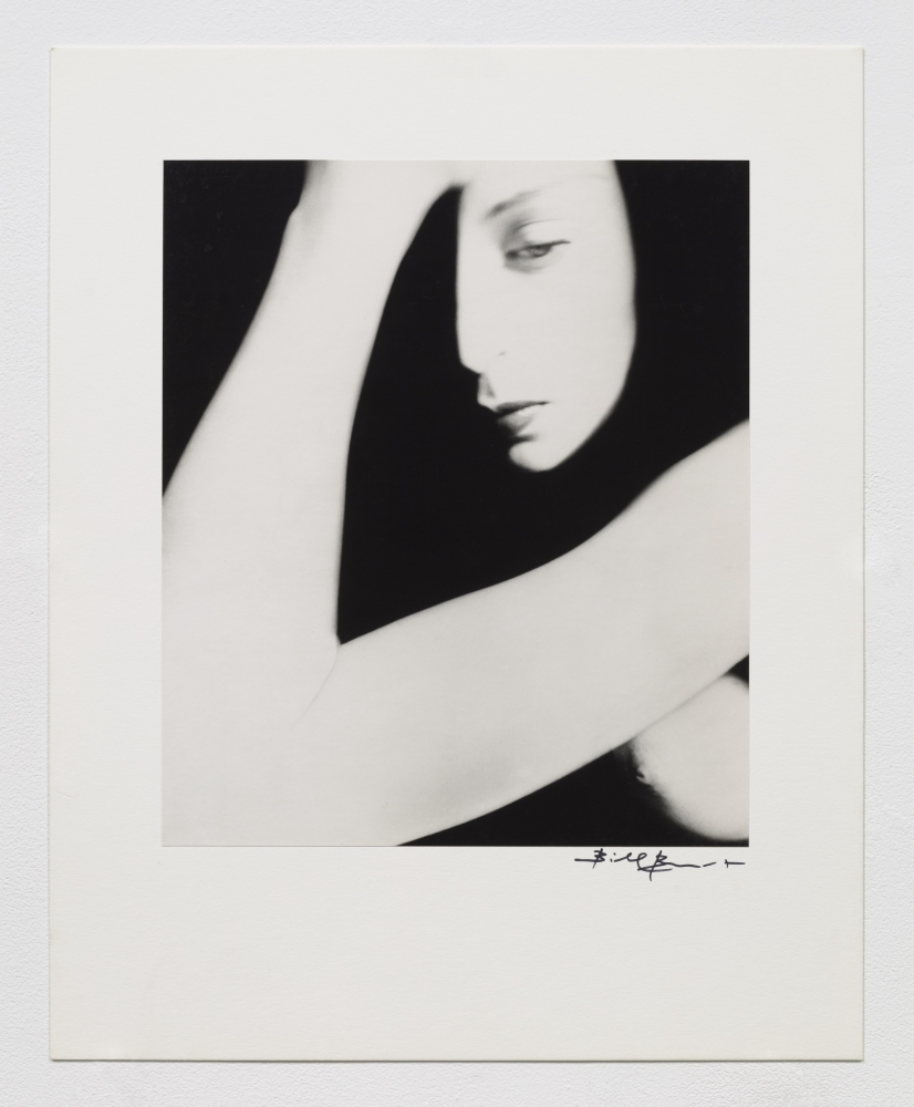 Black and white photographic portrait of nude woman with heavy contrasting shadows.