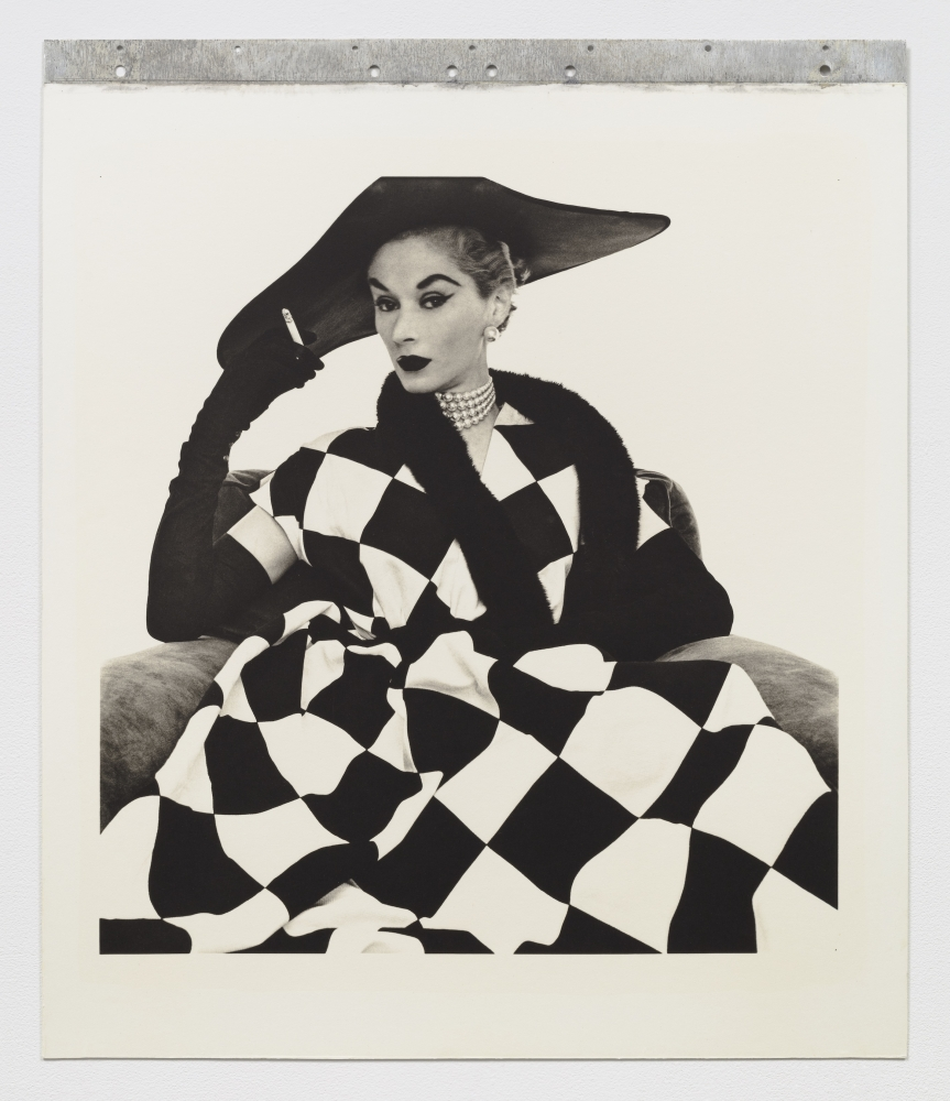Black and white photographic portrait of a woman in checkered clothing.