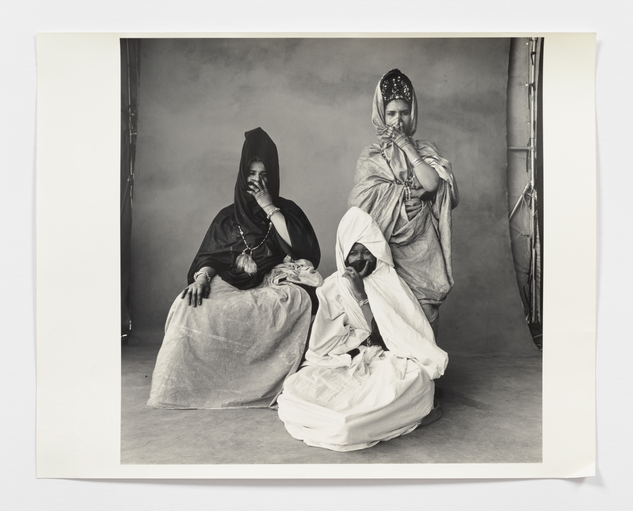 Black and white photograph of three women in drapery fabric.