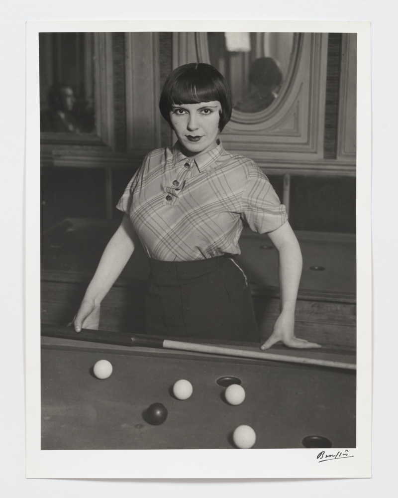 Black and white photographic portrait of a prostitute playing Russian billiards.
