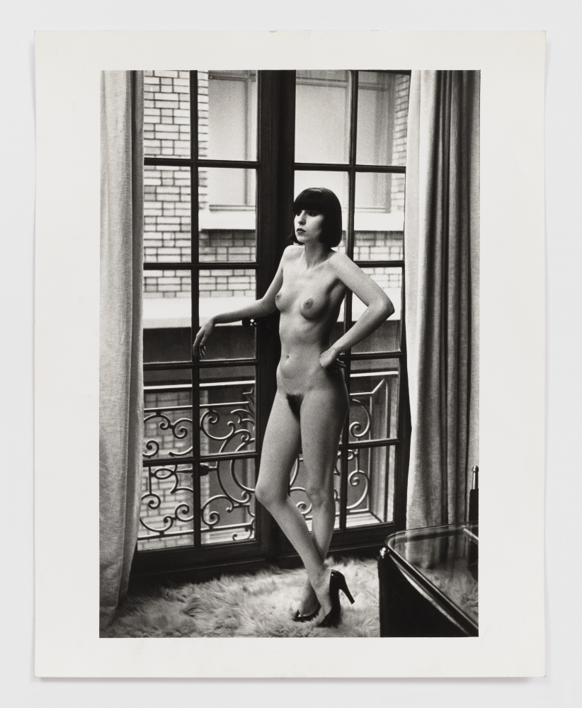 Black and white photographic print by Helmut Newton of a nude woman standing in front of a wndow