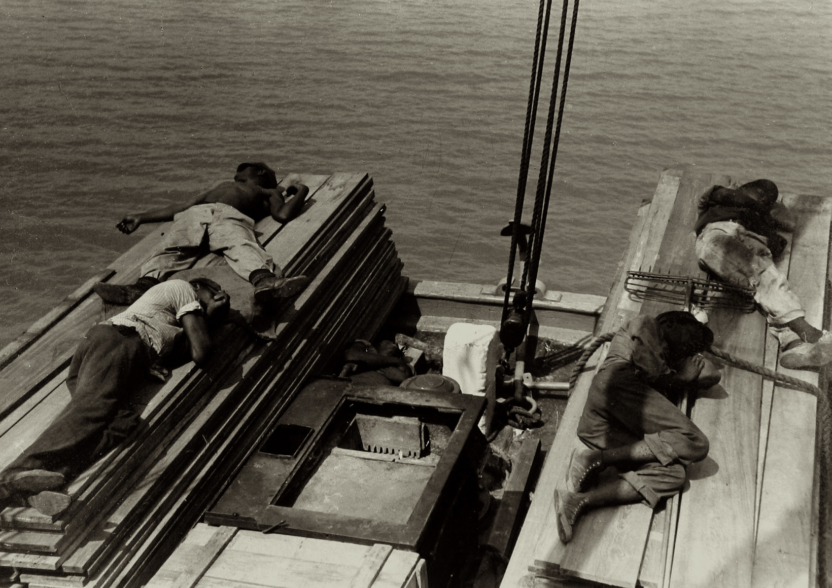 Russell Lee  Untitled (men lying on stacks of wooden planks on boat), c.1937 Gelatin silver print; printed c.1937 9 1/2 x 13 1/2 inches, Howard Greenberg Gallery, 2020