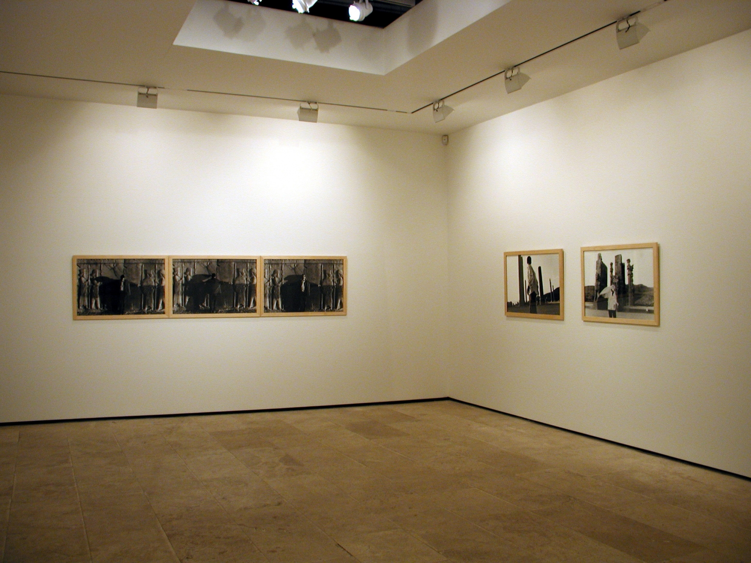 Two groupings of photographs on opposite walls in the exhibition Sadegh Tirafkan at Lehmann Maupin in New York in 2004