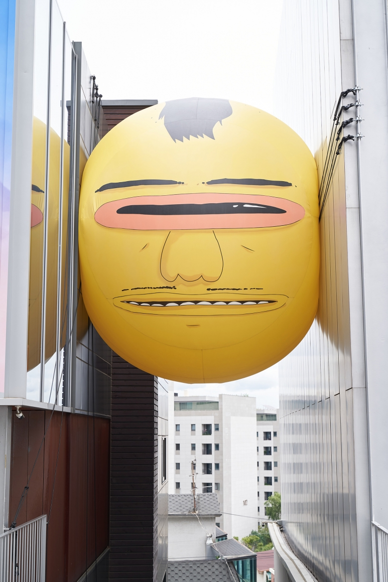 Exterior view of the exhibition OSGEMEOS: You Are My Guest in Seoul. Large yellow balloon with a face squeezed between two buildings