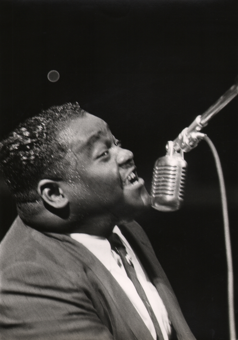 Charlotte Brooks, Fats Domino, c. 1960. Subject sings into a microphone, blurred with motion, facing right.