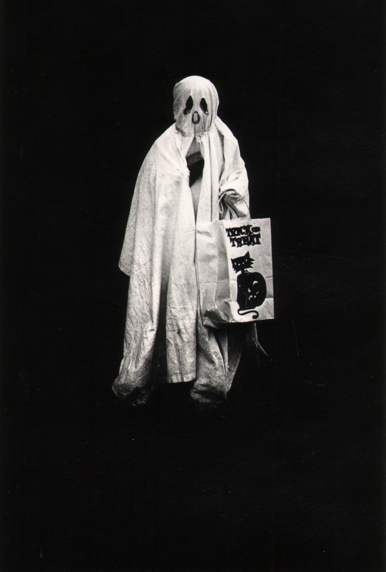 21. Shawn Walker, Halloween, Brooklyn, 1960s. Figure in a draping white ghost costume faces the camera holding a trick-or-treat bag. Background is completely black.