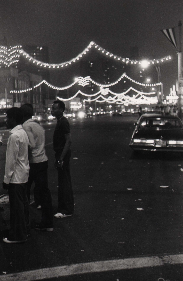 17. Anthony Barboza, Coney Island, NY, 1970s. Three figures gathered on the left of the frame. Cars and string lights are out of focus in the street behind them.