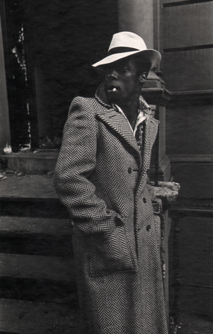 09. Anthony Barboza, Harlem, NY, 1970. A man standing on the sidewalk with hands in a long coat. He wears a white hat, body facing the right with his face turned left.