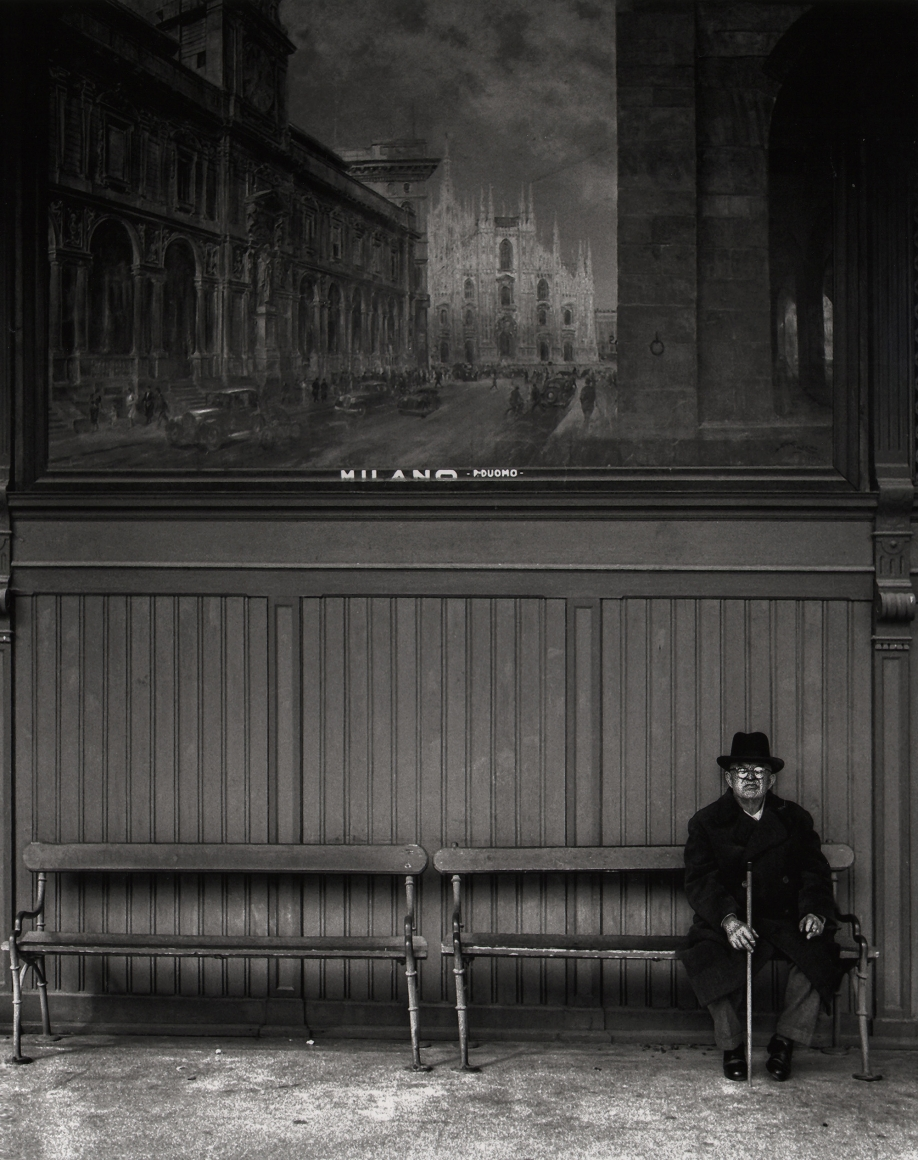 Nino Migliori, Northern People, 1950. A man with a cane seated on a bench. A mural of Milan is on the wall behind him.