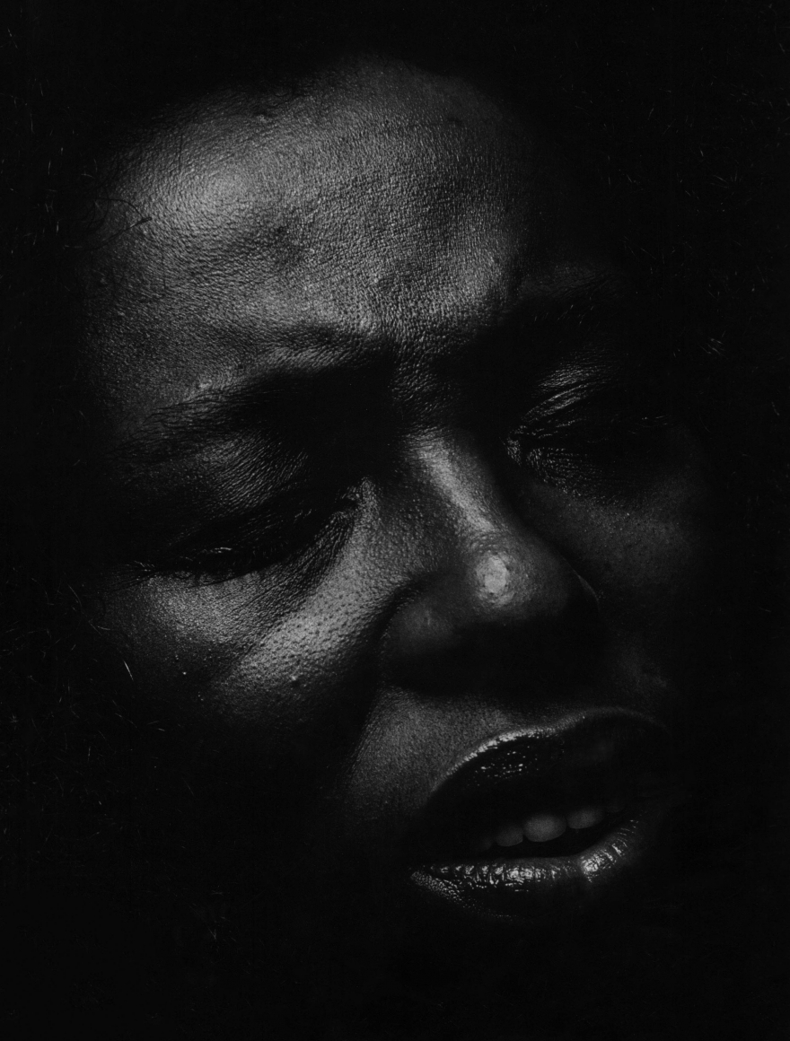 06. Anthony Barboza, Roberta Flack, singer, for Essence Magazine, 1970s. Close up of the singer's dimly-lit face facing slightly to the right, with eyes closed and lips slightly parted.