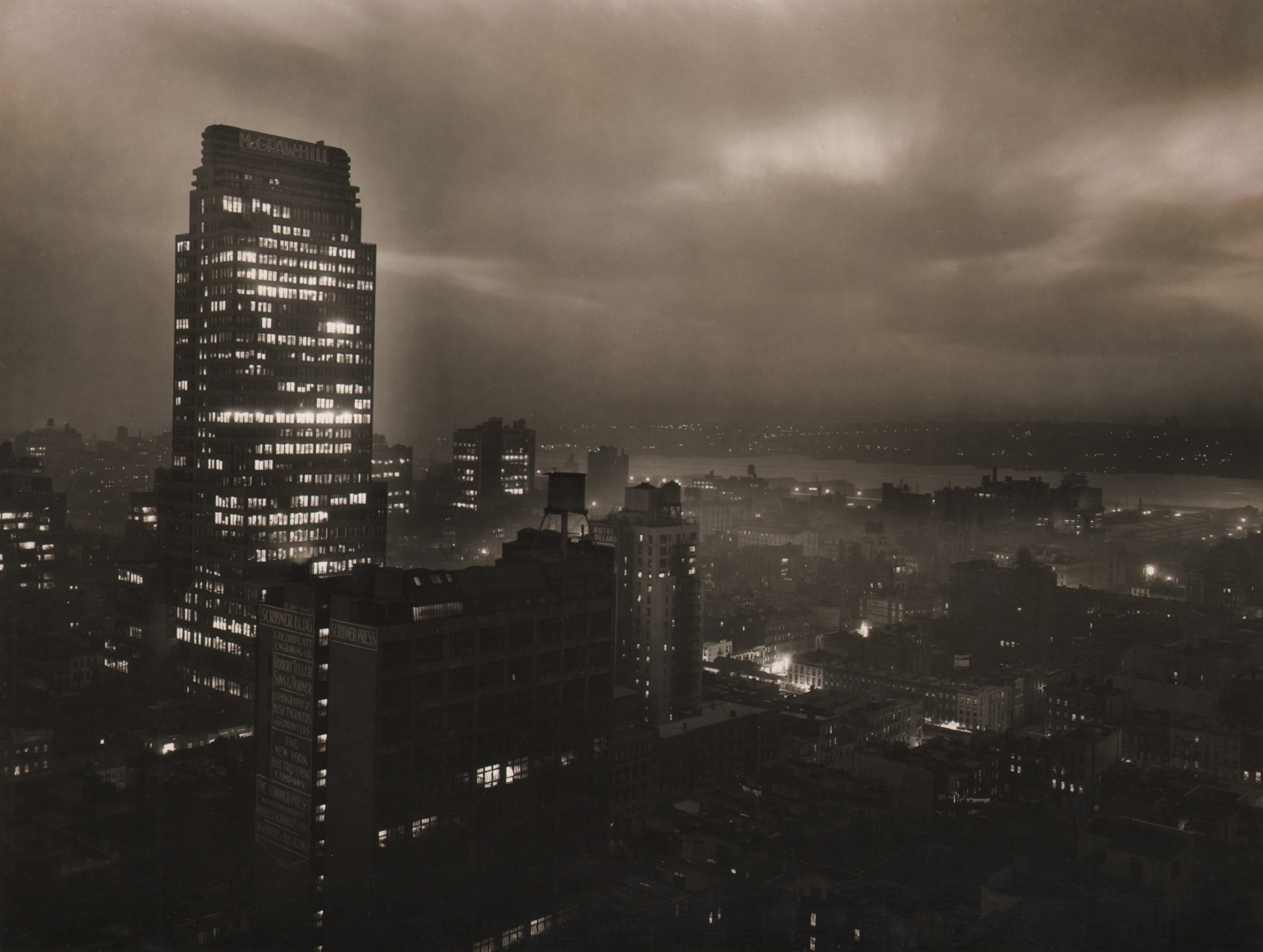 Paul J. Woolf, McGraw Hill Building & Hudson River from Roof of the Hotel Lincoln, c. 1935. Night time cityscape with tell McGraw Hill Building in center left of the frame beneath overcast sky.