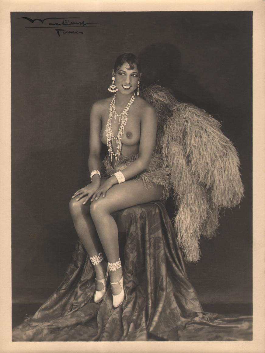 Lucien Walery, Josephine Baker, c. 1925. Subject poses seated, topless, in large jewelry and feathers.