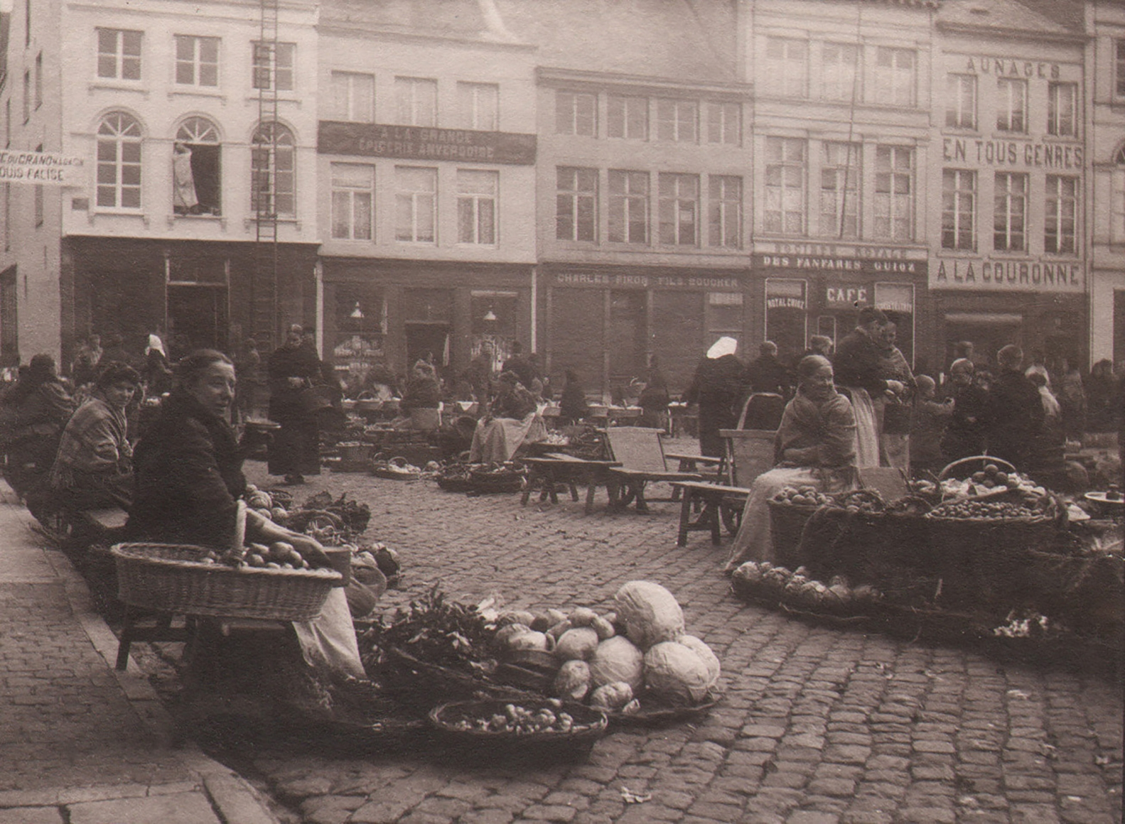 23. Léonard Misonne, Untitled, c. 1930. Market vendors on a cobbled commercial street with various forms of produce. Sepia-toned print.