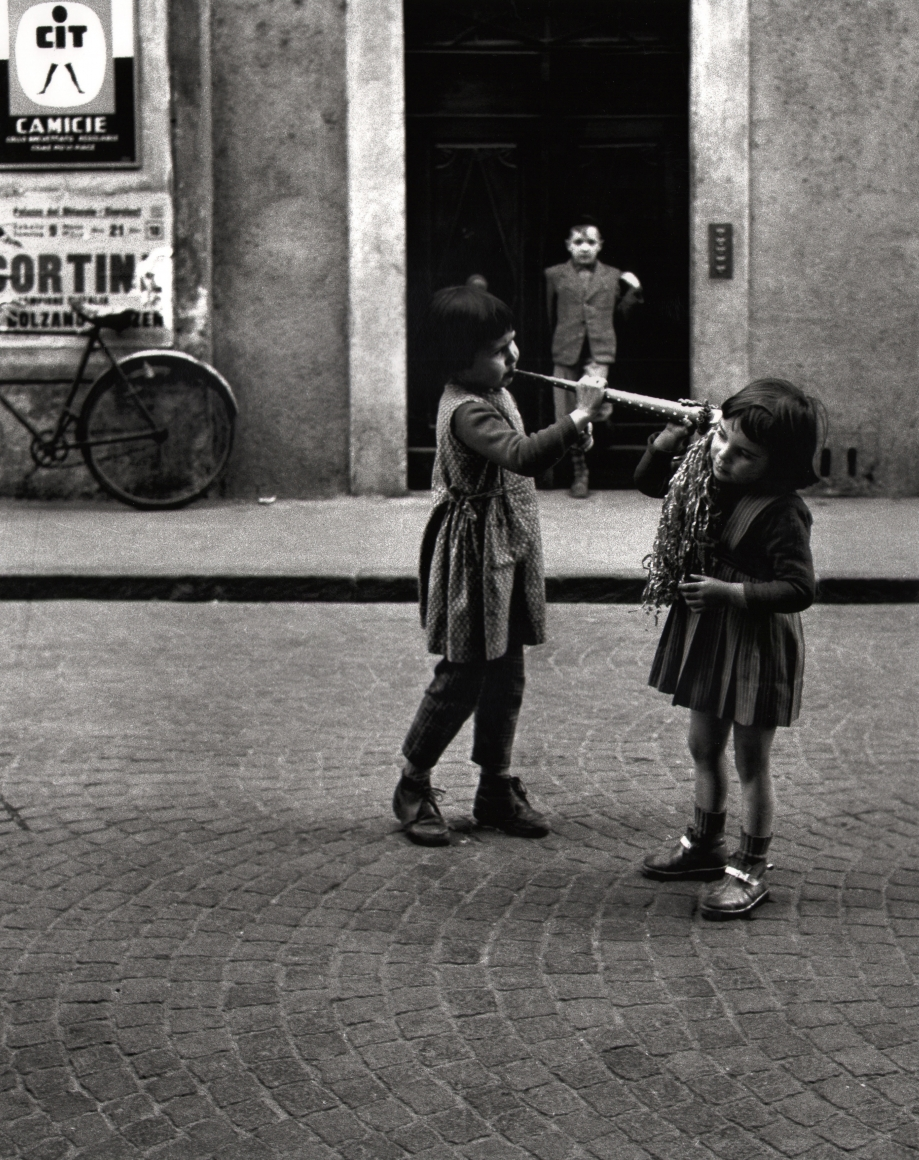 Nino Migliori, People of Emilia, 1950. Street scene featuring three children. One boy stands in a doorway in the background, while two girls play with a wind instrument in the foreground.