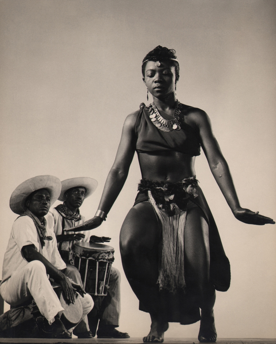 Gjon Mili, Pearl Primus, c. 1943. Subject crouches with eyes closed to the right of the foreground, while two male musicians look to her while playing drums in the background.