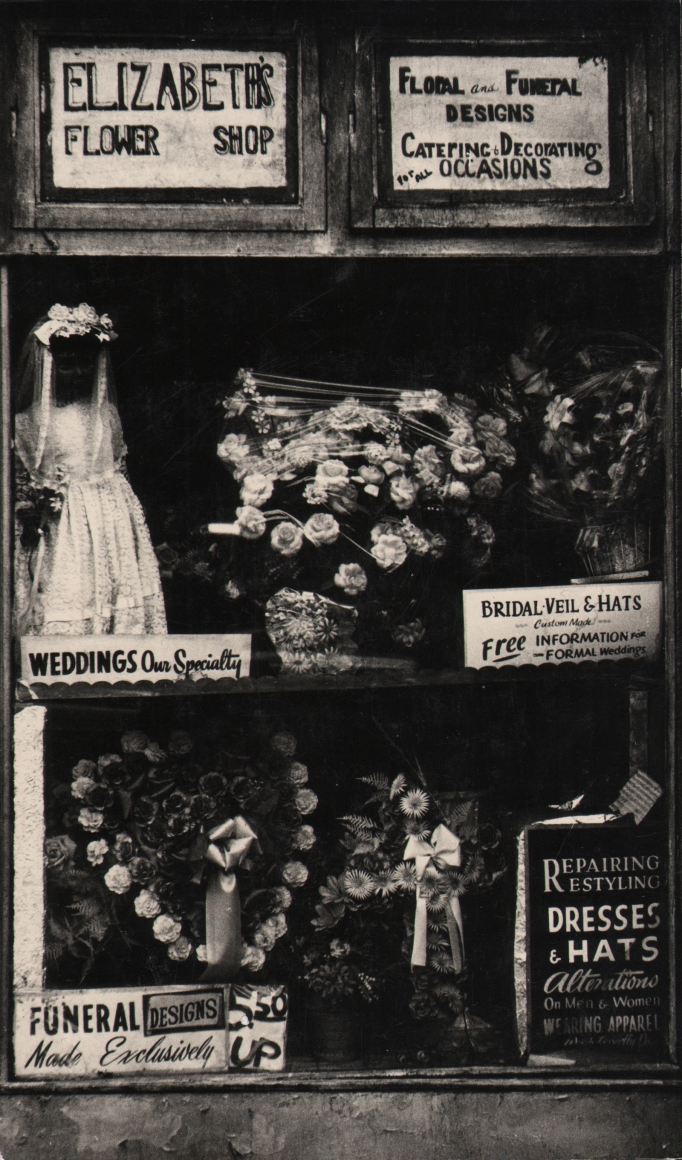 """27. Beuford Smith, Harlem, NY, n.d. Window display of """"Elizabeth's Flower Shop"""" with various floral arrangements on offer."""