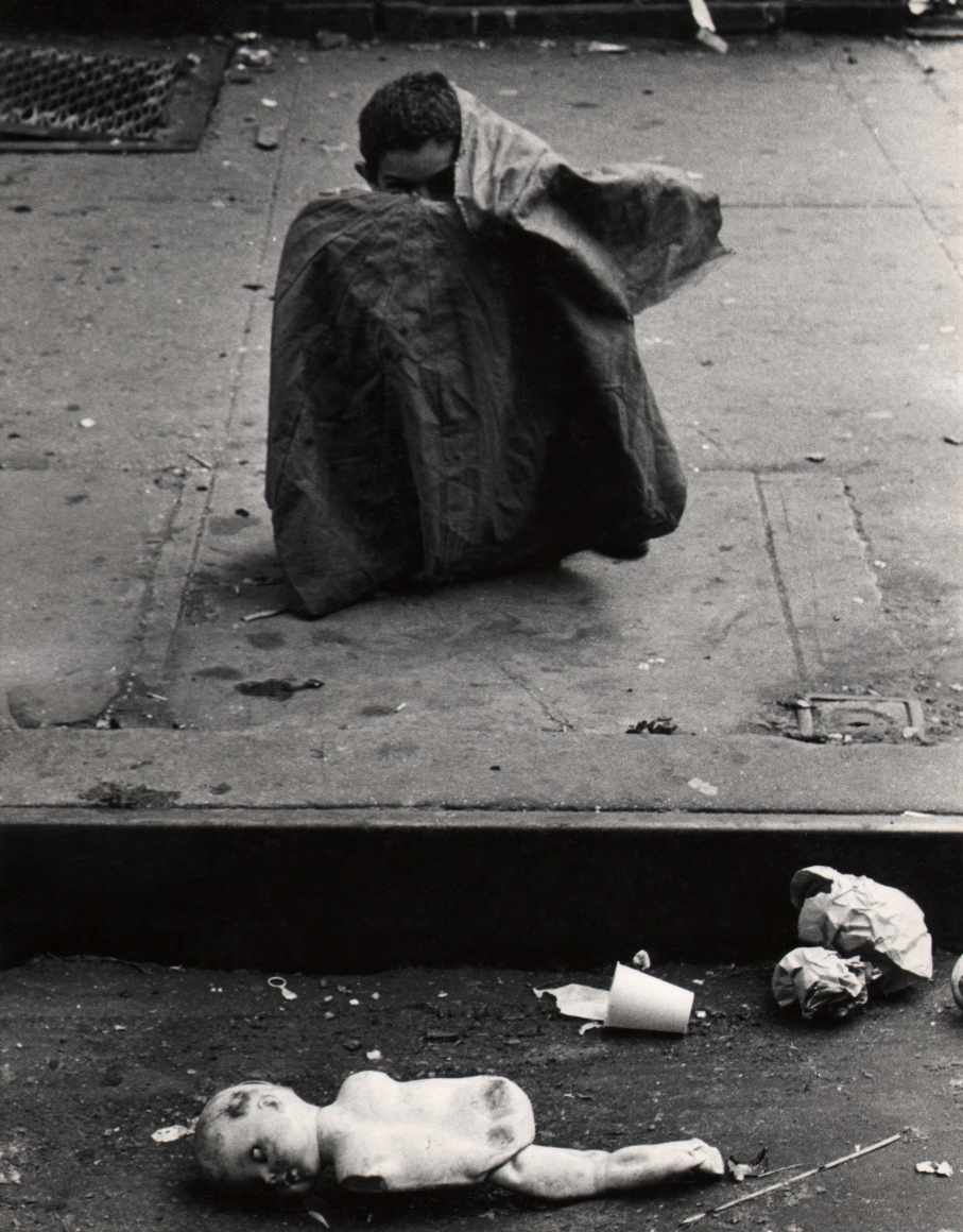 34. Beuford Smith, Boy & Doll, Lower East Side, NYC, 1966. A young boy sits on the sidewalk with most of his body covered by some sort of cloth; a broken doll and other trash is on the street in front of him at the bottom of the frame.