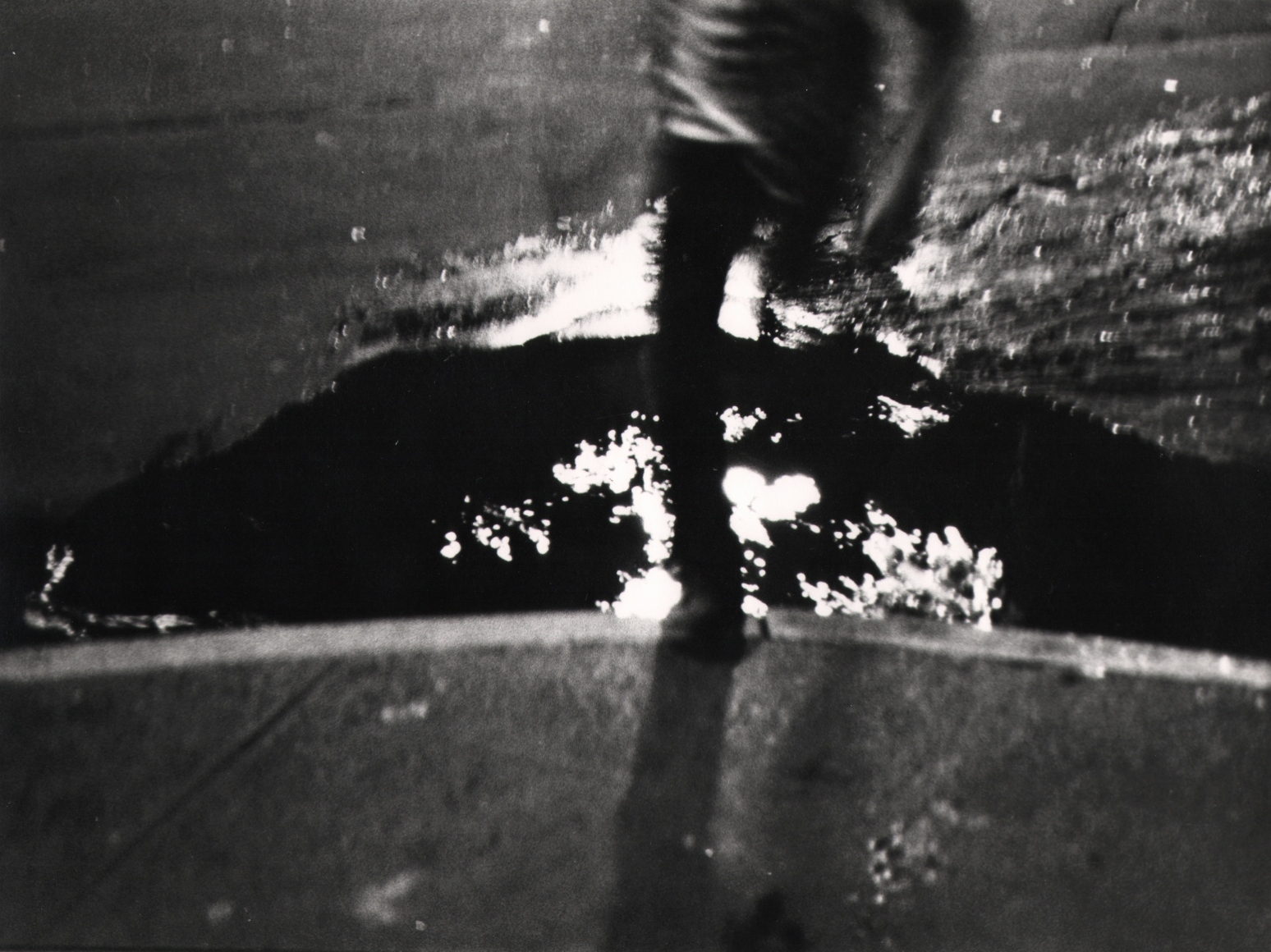 37. Beuford Smith, Untitled, c. 1970. Motion-blurred, dark image of the lower body of a boy jumping over a puddle.