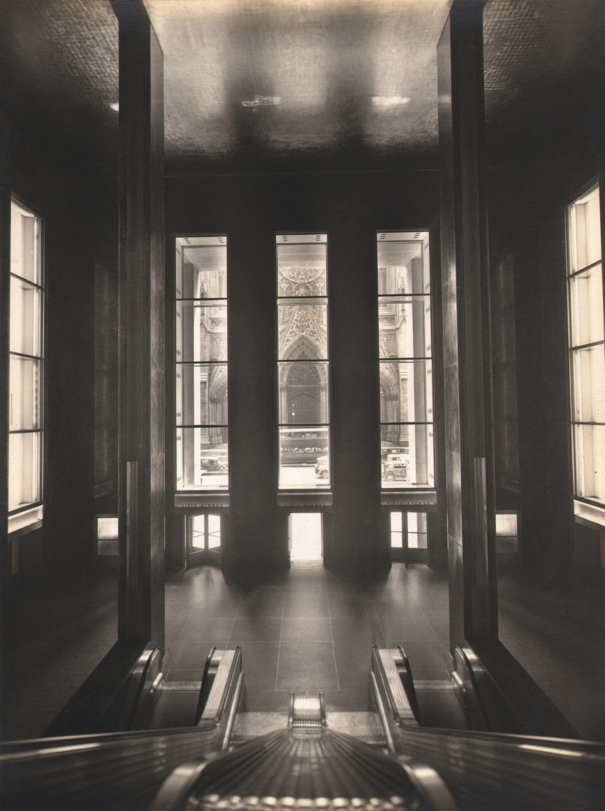Paul J. Woolf, International Building Lobby, c. 1935. Lobby with tall windows photographed from between the top of two escalators. Cathedral entrance opposite can be seen through center window.