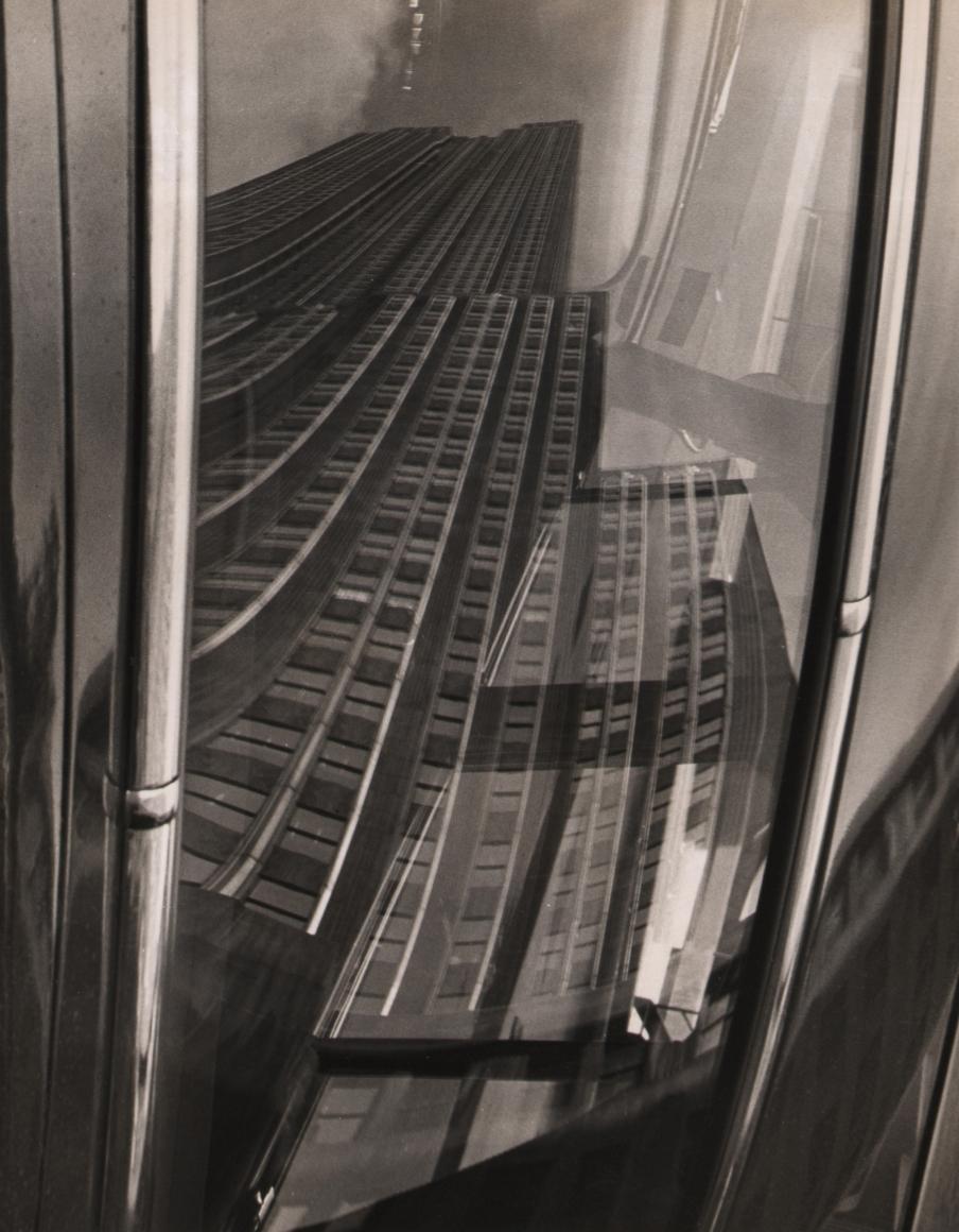 28. Fritz Neugass, Empire State Building Reflection, c. 1948. Distorted reflection view of the Empire State Building's base, looking upward.