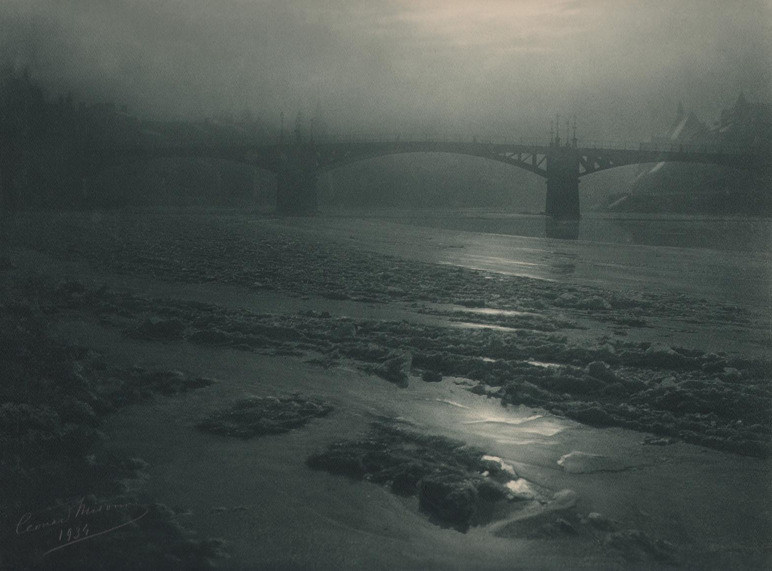 12. Léonard Misonne, Hiver à Dinant, 1934. Partially frozen body of water running under a bridge in hazy light. Gray/green-toned print.