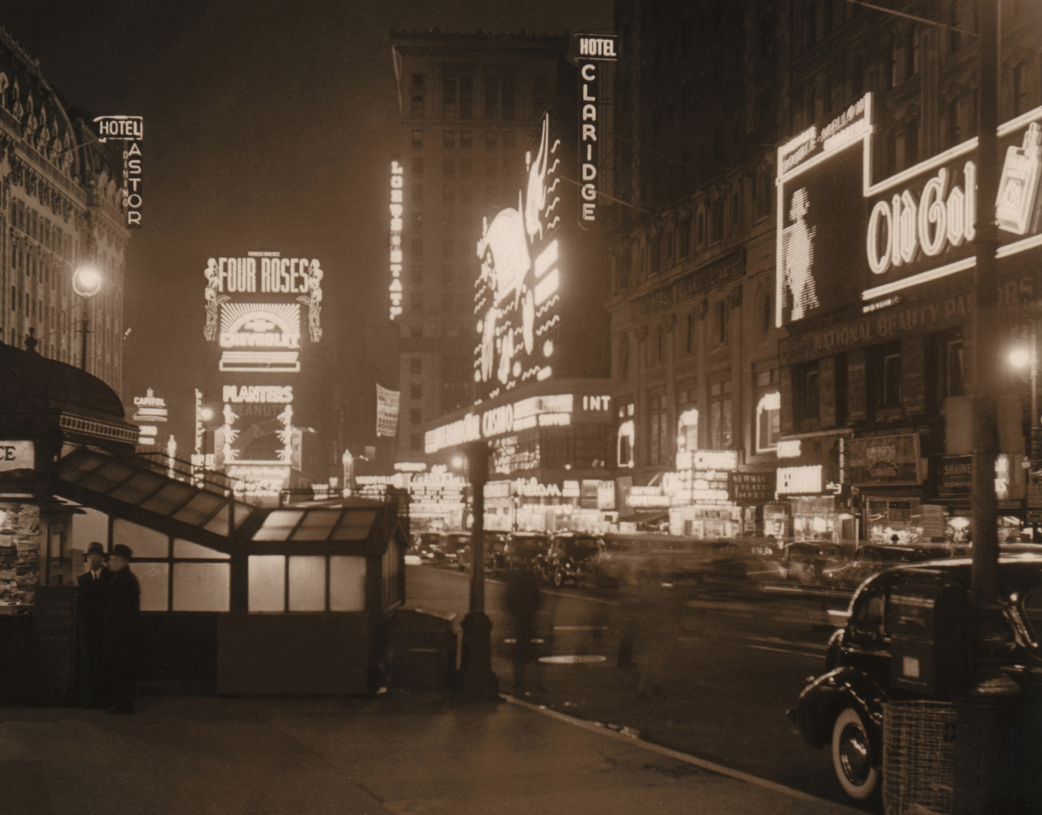 Paul J. Woolf, Broadway, c. 1935. Night time street scene featuring lit neon hotel, casino, and advertising signs.