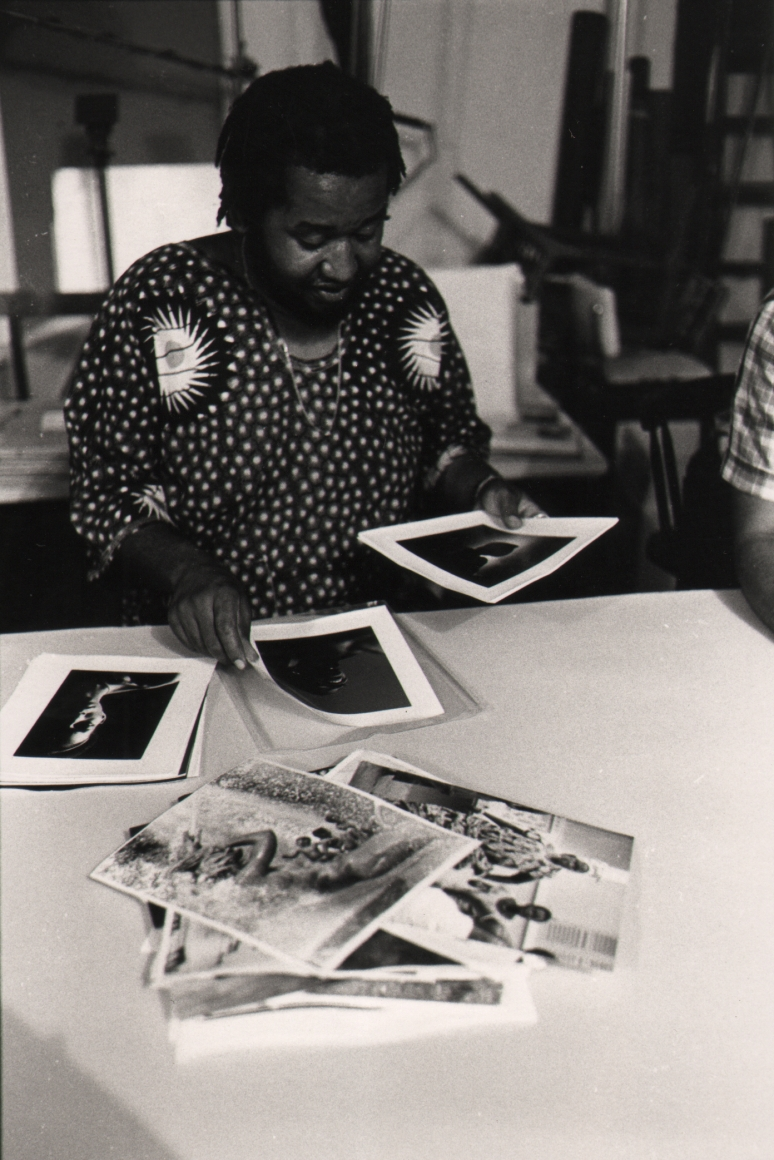 01. Anthony Barboza, Shawn Walker, International Black Photographers Annual, 1973. A man in a patterned shirt flips through a stack of photographs on a white table.