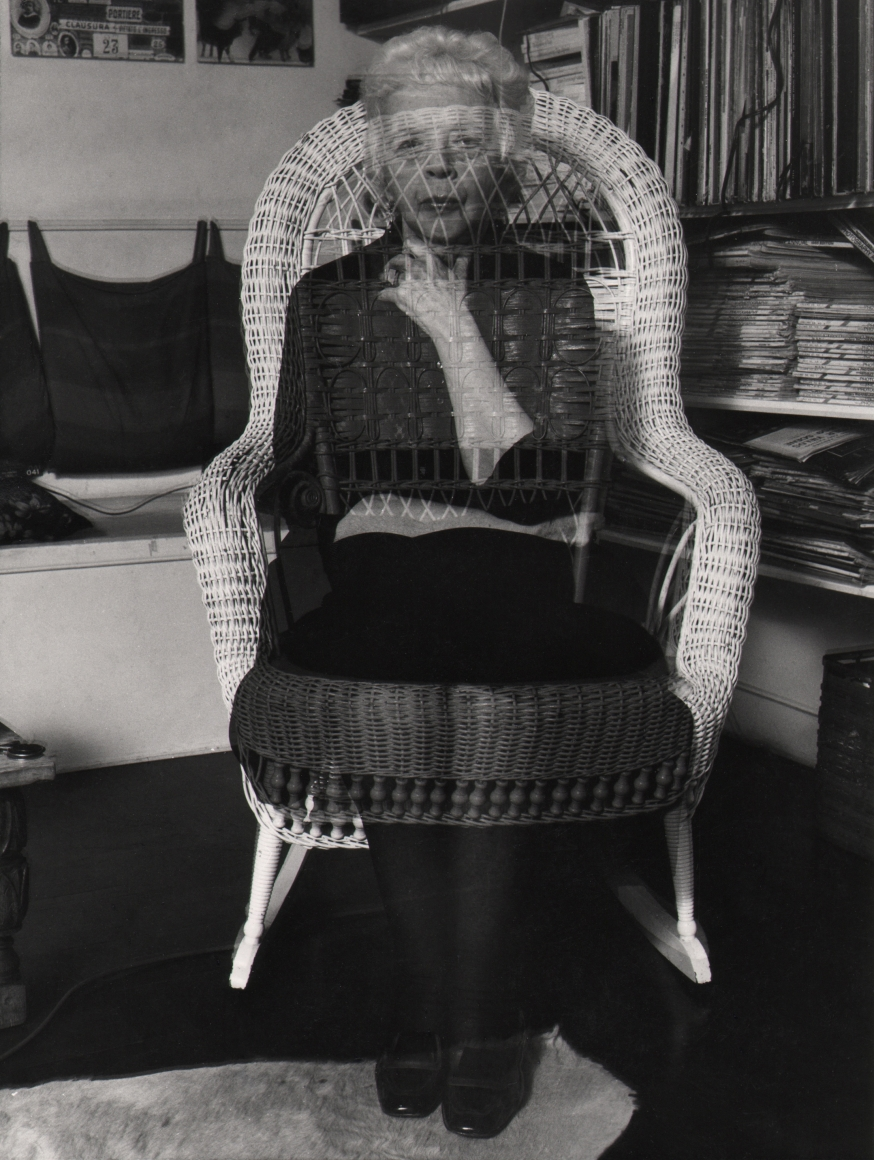 02. David Attie, Lisette Model, 1972. Portrait of a woman seated on a wicker chair. Double-exposure affect makes the woman appear semi-transparent.