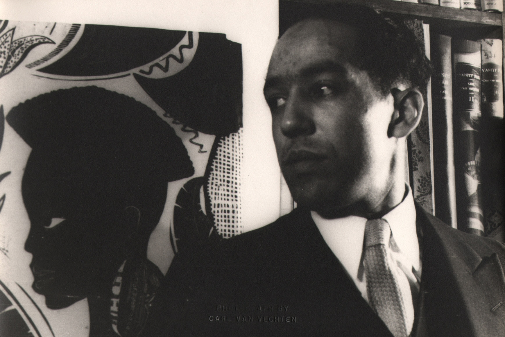 Carl Van Vechten, Langston Hughes, 1932. Subject poses looking to the left beside a painting with the figure in the same pose.