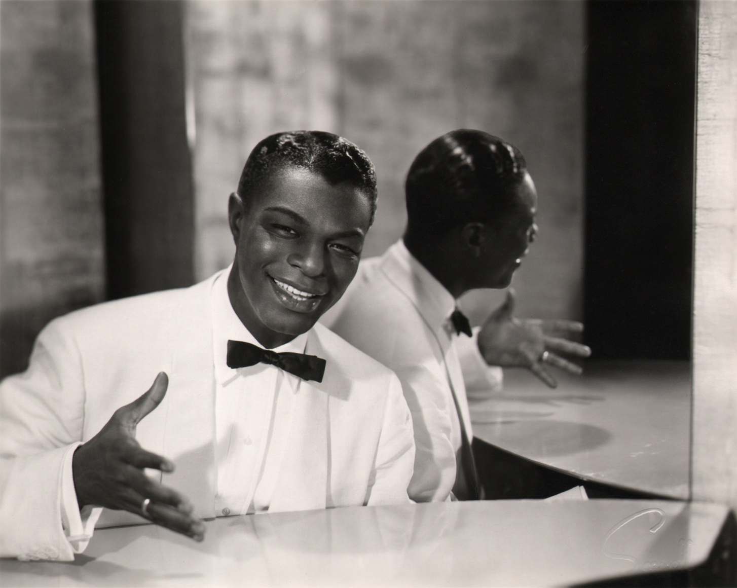 Wallace Seawell, Nat King Cole, c. 1955. Subject is seated in a white suit at the piano in front of a mirror, gesturing and smiling towards the camera.