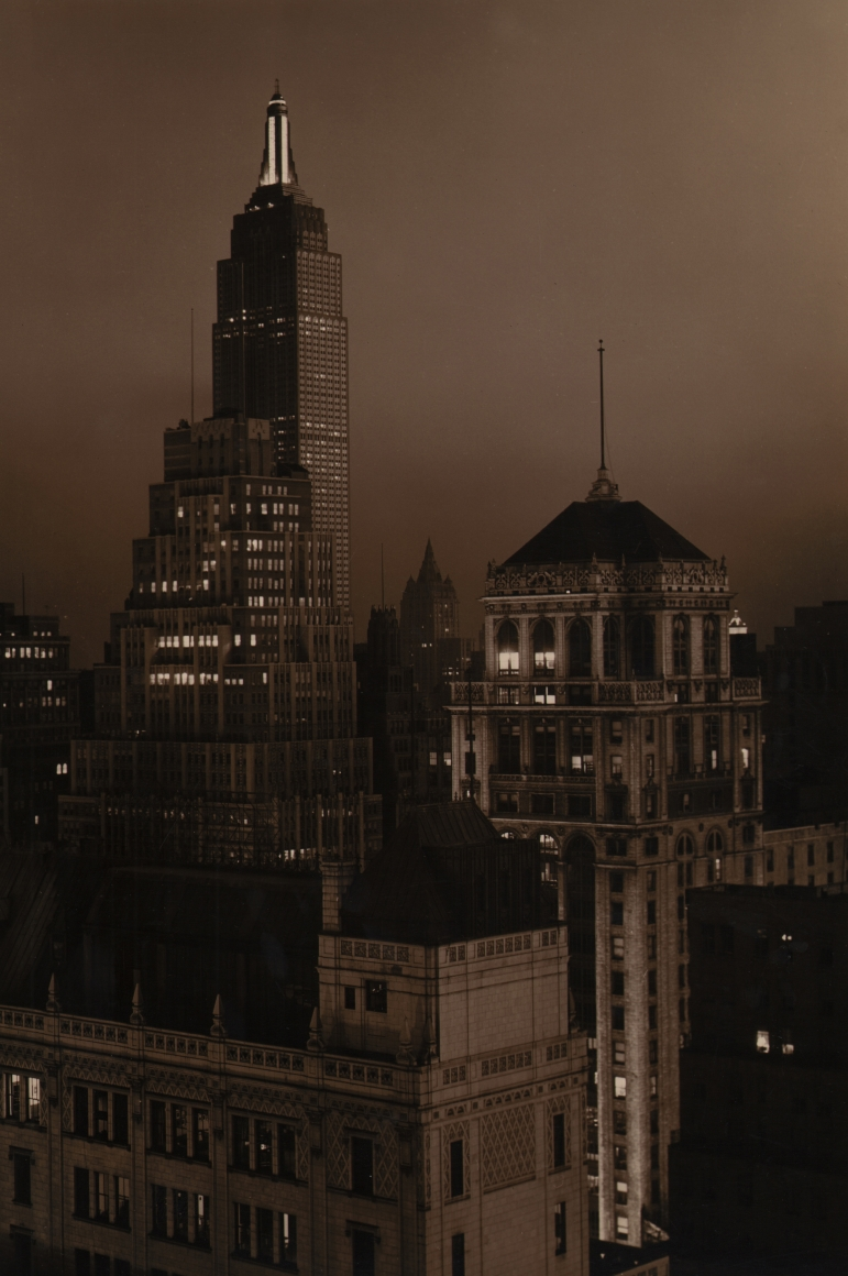32. Paul J. Woolf, Times Building Looking South, c. 1935. Night time sepia tone cityscape in a vertical composition. The Empire State Building is in the top left of the frame.