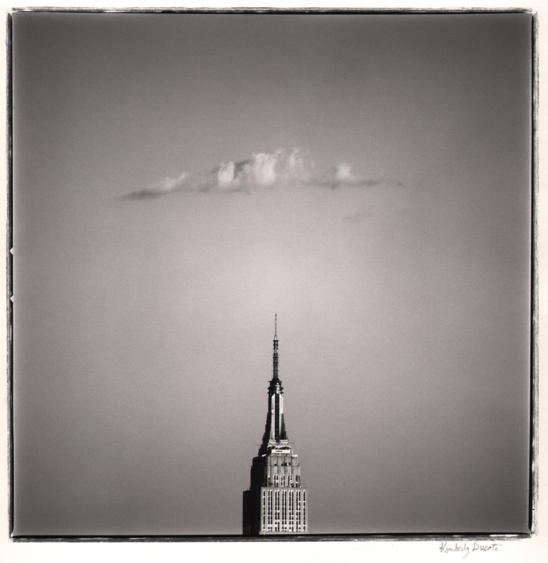 07. Kimberly Ducoté, Empire State Building, 1990. Distant, head-on view of the top of the Empire State Building, which occupies the lower center of the frame. Above it is a single cloud.