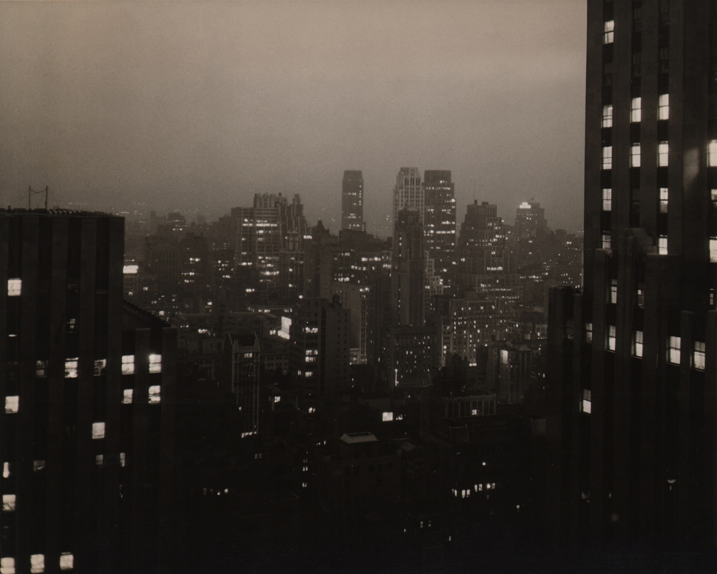 Paul J. Woolf, New York Skyline at Night, c. 1935. Night time cityscape. Two close buildings on the left and right foreground with skyscrapers across the background center.