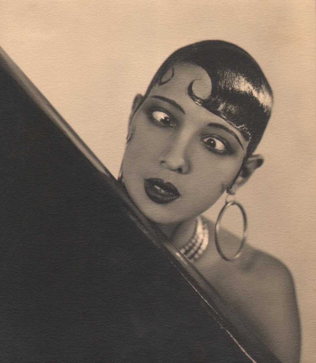 George Hoyningen-Huene, Josephine Baker, c. 1929. Subject crosses her eyes and wears large hoop earrings, resting her chin on a black piece of furniture.