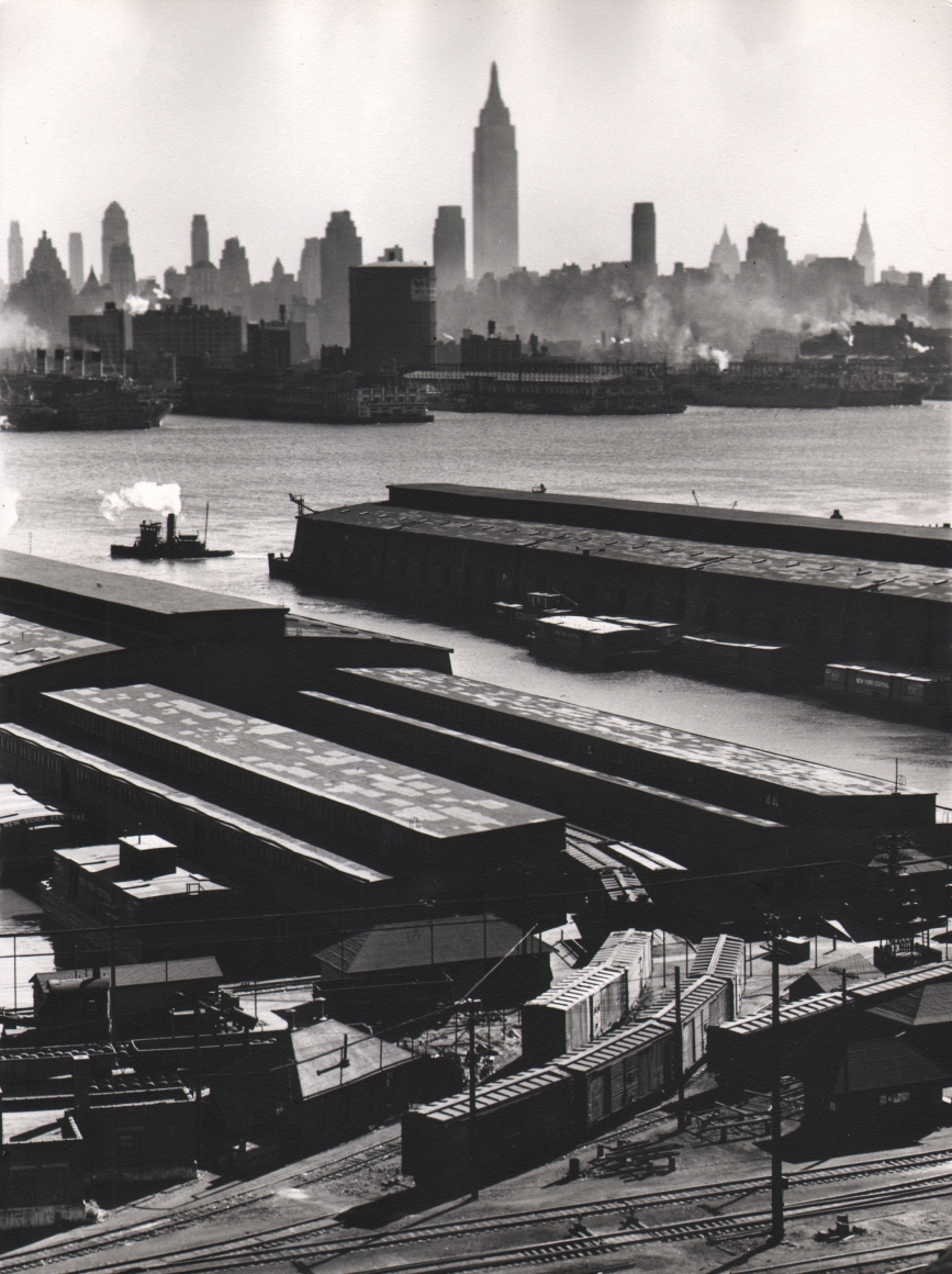 20. Esther Bubley, Weehawken, New Jersey. View looking east from 50th Street and East Boulevard showing New York Central piers, Hudson River and Midtown Manhattan skyline, 1946.