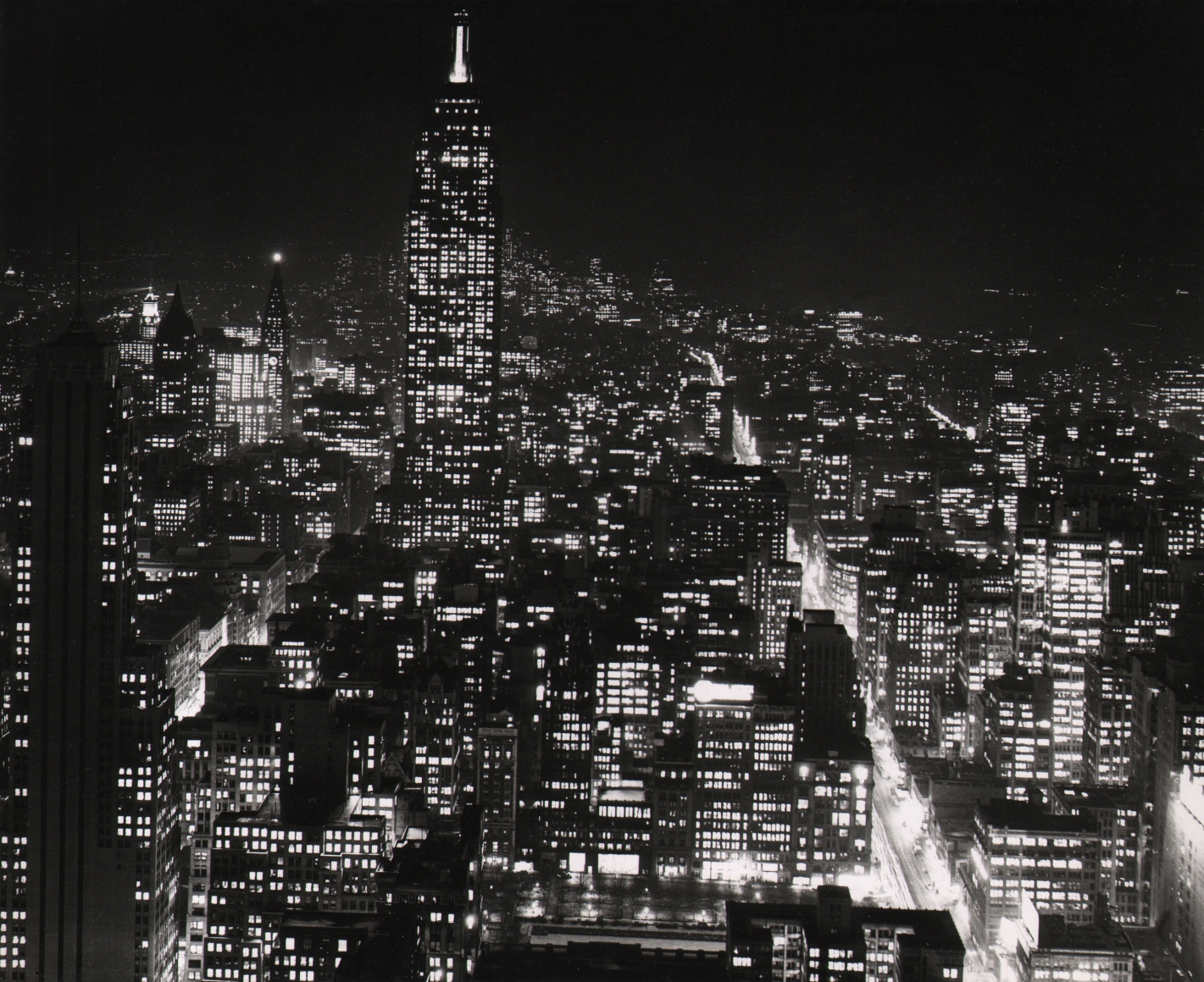 32. Sheldon Hine, New York City at Night Atop Radio City, c. 1938. Nighttime cityscape in a horizontal composition with the Empire State in the top left quadrant of the frame.