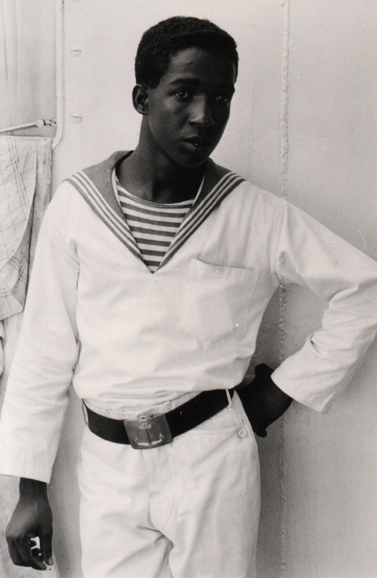 25. Shawn Walker, Untitled, c. 1970. A man stands in a white sailor's uniform with one hand at his hip.