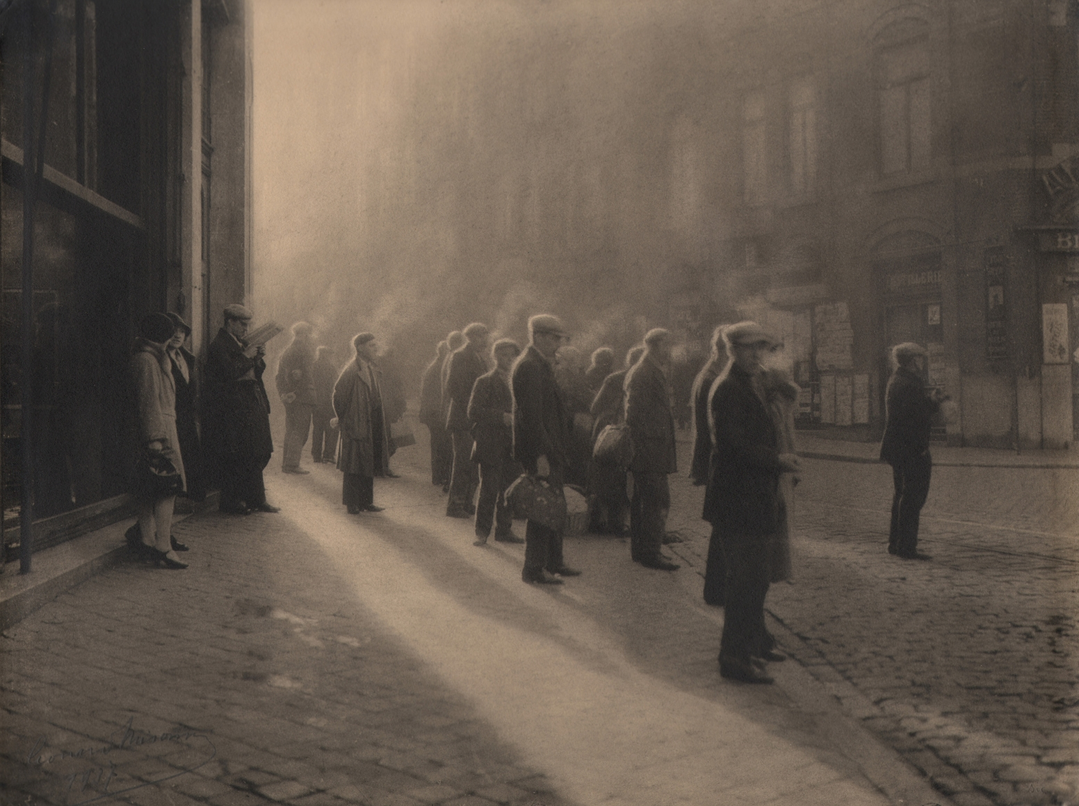 08. Léonard Misonne, Première cigarette, 1927. Various figures, mostly capped men, stand on the sidewalk, cigarette smoke rising above them. Sepia-toned print.