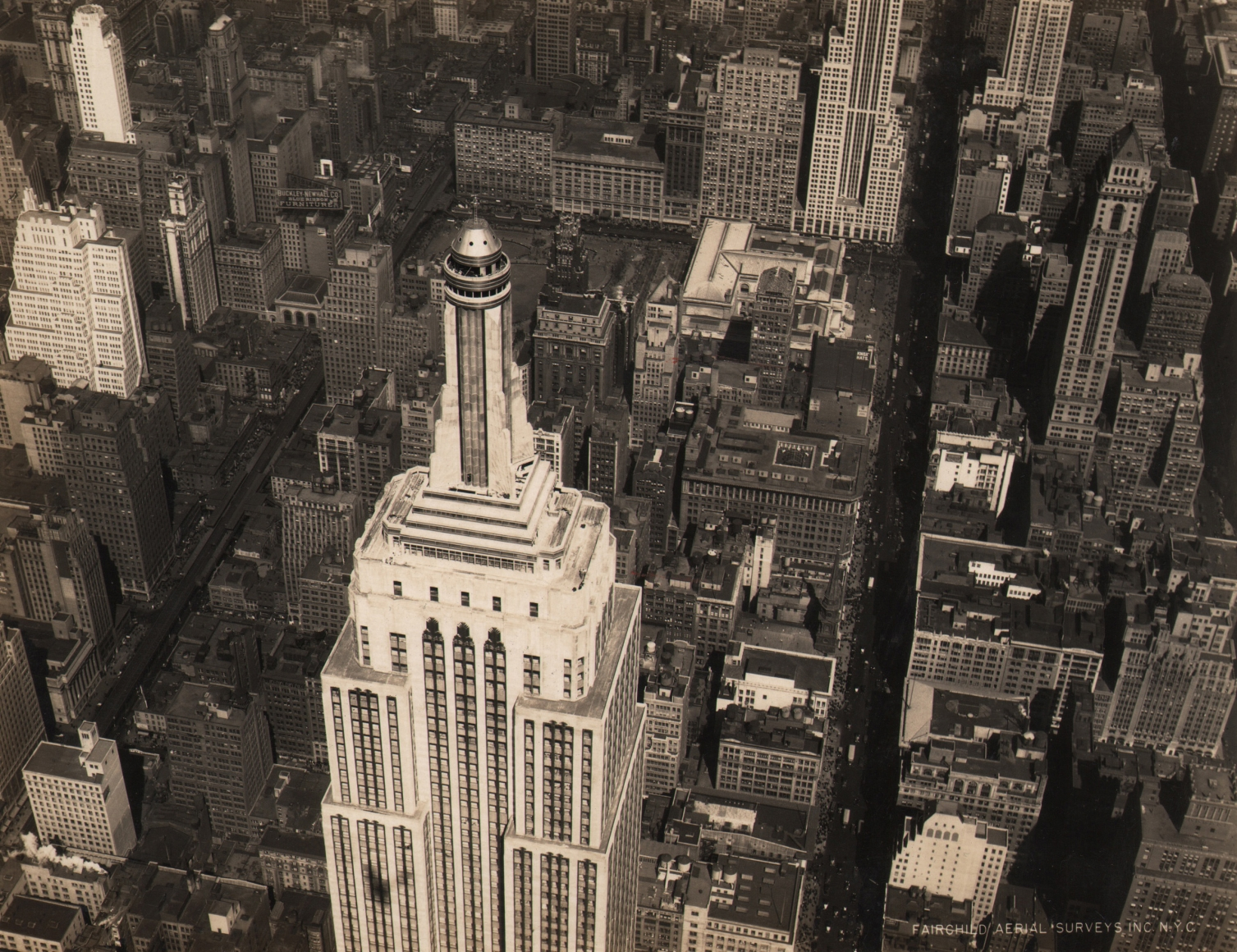 24. Fairchild Aerial Surveys, Empire State Building, Midtown, NYC, 1931. Aerial view of the top half of the Empire State Building, photographed from the above and to the right. Other city buildings and streets can be seen below.