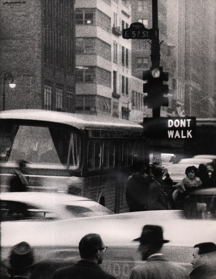 """28. David Attie, Untitled, c. 1965. Street scene featuring a traffic light, crosswalk signal that reads """"Don't Walk,"""" a sign reading """"E 57 St"""", vehicles, and a number of pedestrians."""