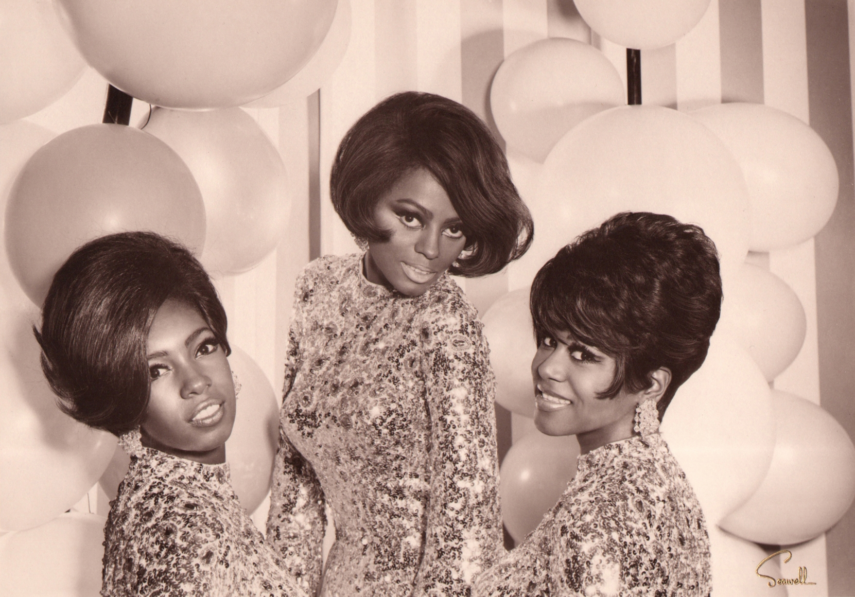 Wallace Seawell, Diana Ross & The Supremes, 1967. The three subjects pose in sparkling dresses against a striped wall with white balloons.