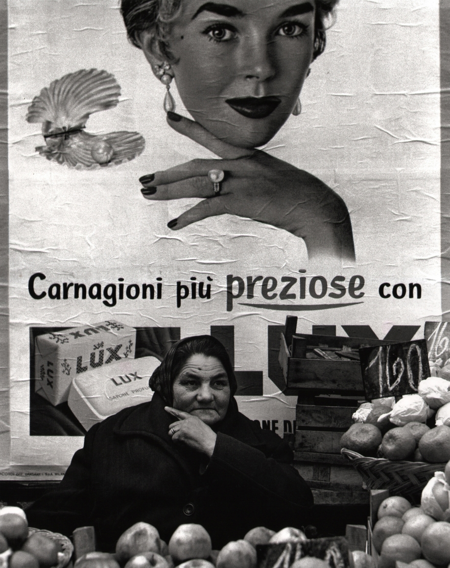 Nino Migliori, Northern People, 1953. A middle-aged fruit vendor poses similarly to the woman in the advertising illustration behind her.