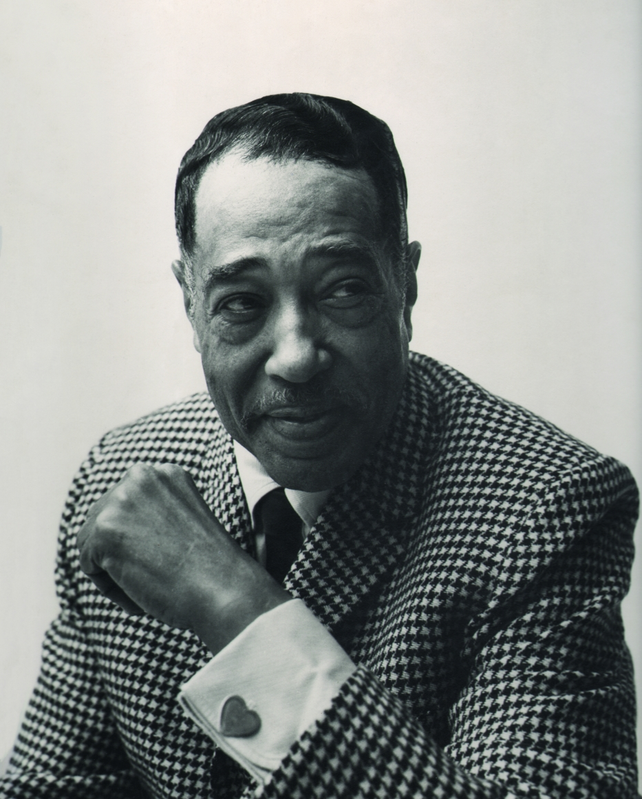 Chuck Stewart, Duke Ellington, 1955. Subject smiles with eyes cast to the right, with one arm raised in front of his chest to reveal a heart-shaped cufflink.