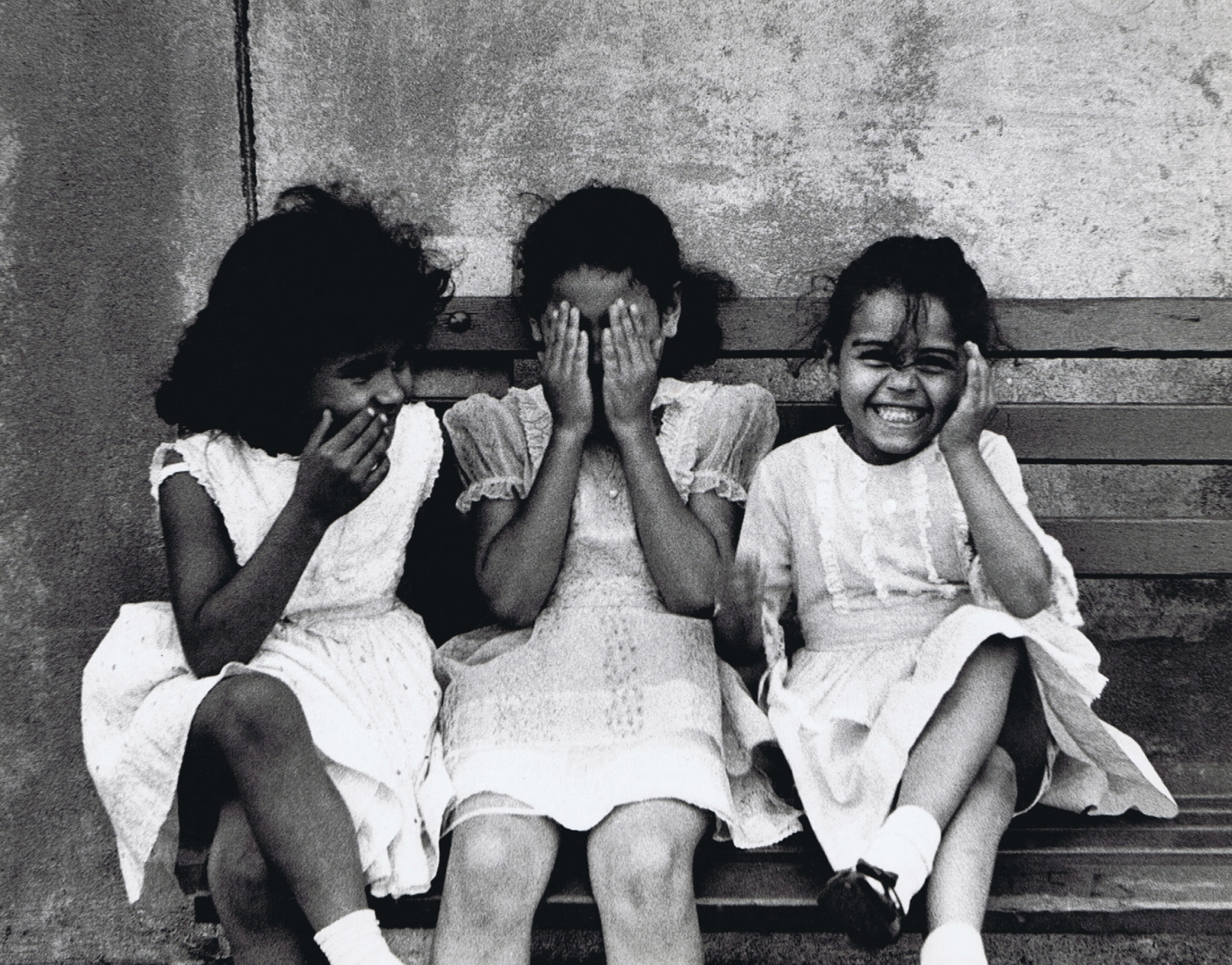 35. Beuford Smith, Three Girls, Bronx, 1968. Three girls in white dresses seated on a bench. From left to right, one has a hand to her mouth, the next has hands covering her eyes, the last has one hand covering an ear.