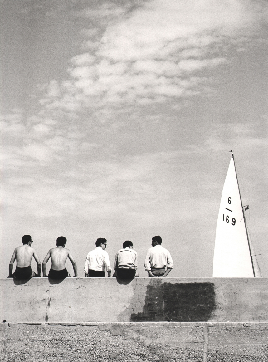 Nino Migliori, Quattro Con, 1955. Five men seated on a wall photographed from the back. A ship's sail is in the right of the frame.