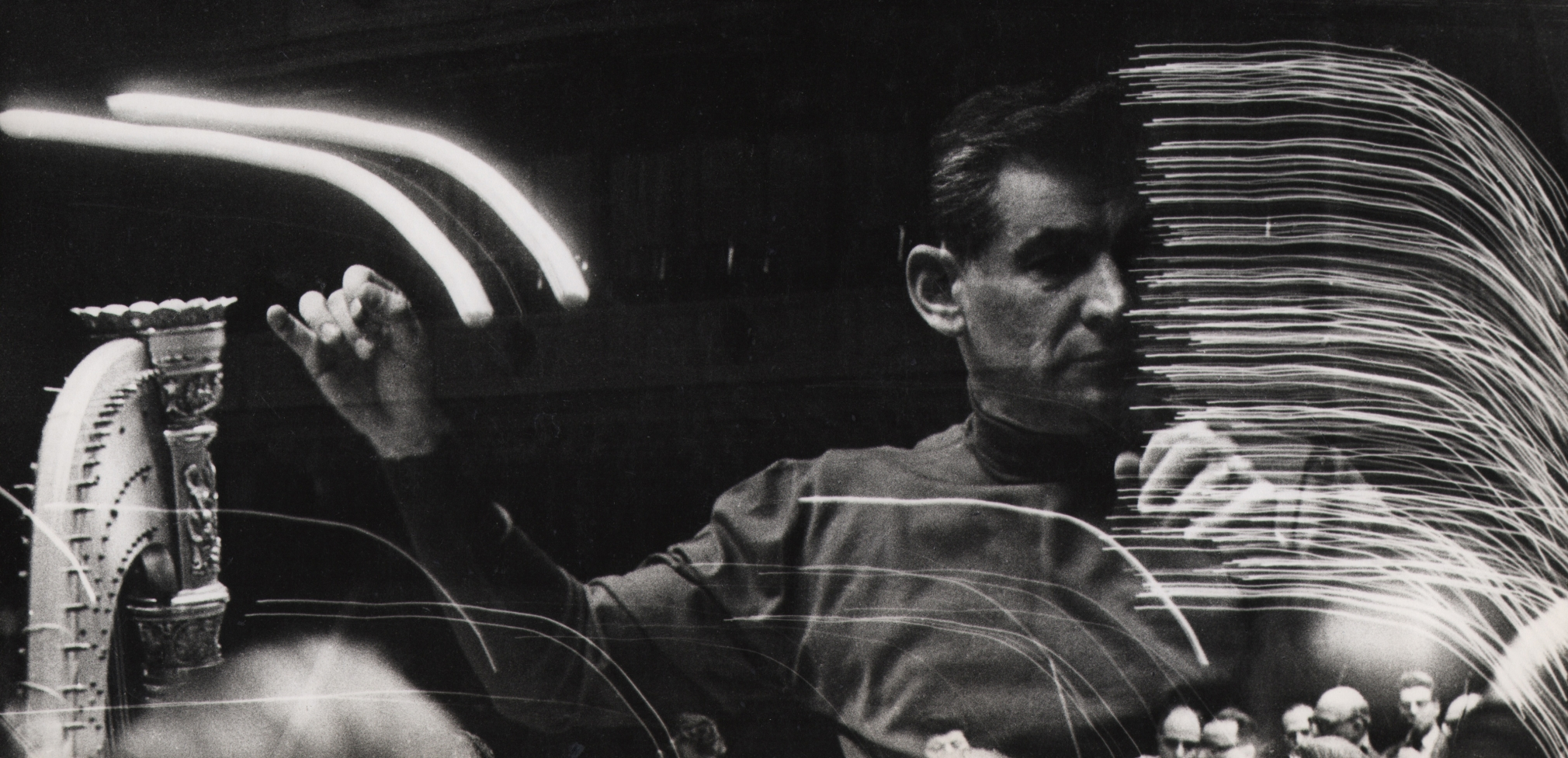 06. David Attie, Leonard Bernstein, rehearsal at Carnegie Hall, 1959. Multiple-exposure photograph featuring a man with arms raised as if conducting and streaks of light.