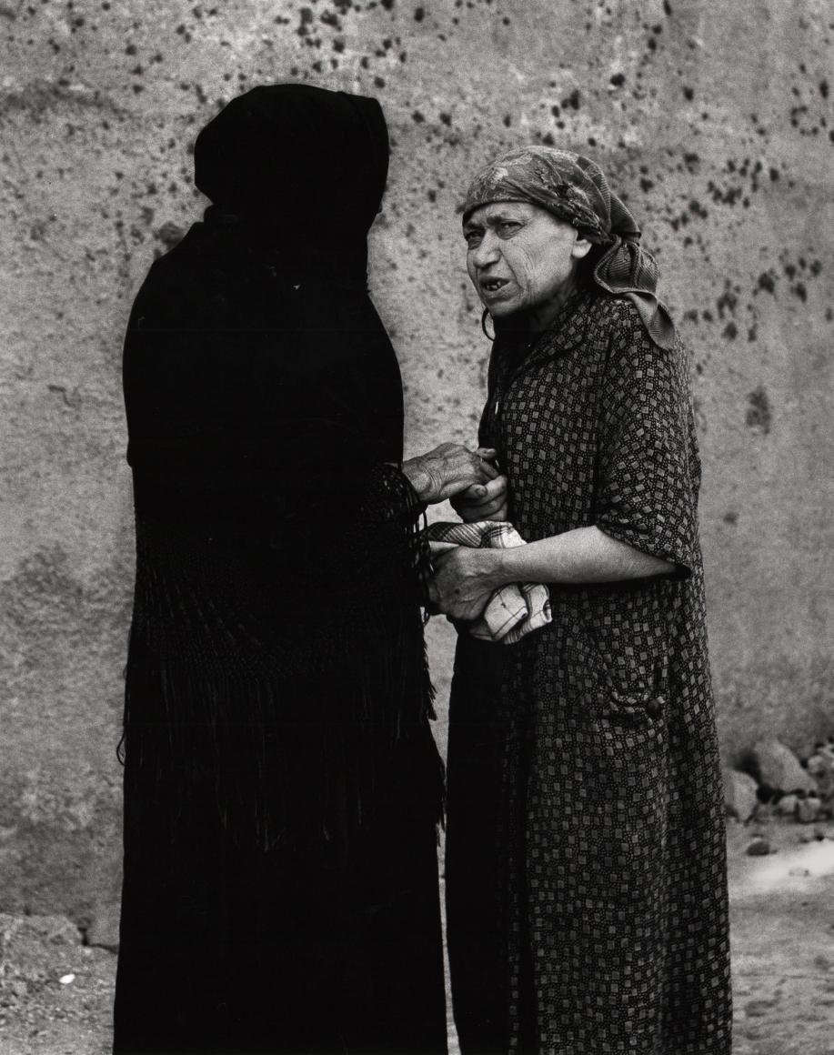 Nino Migliori, The Widow, 1956. Two woman talk on the street. One is wearing all black.