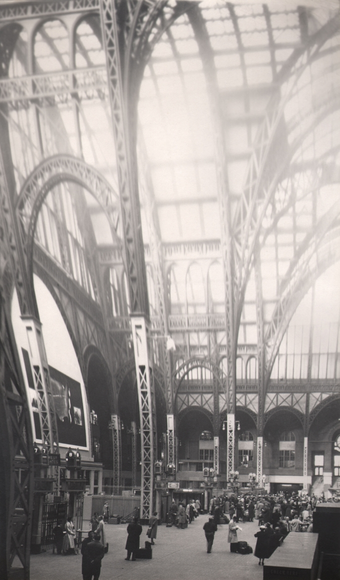33. David Attie, Penn Station, 1957. Vertically elongated image of the pillars and skylights of the original Penn Station building. Various commuters can be seen in the lower portion.