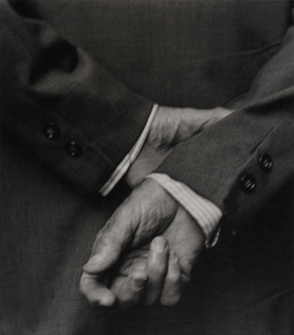 28. Beuford Smith, Two Buttons, n.d. Close up of one hand holding the opposite wrist behind a suited man's back.