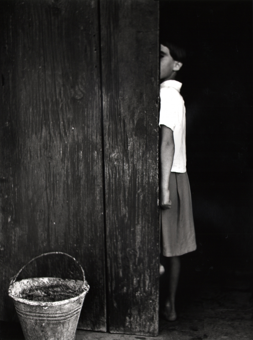 Nino Migliori, People of Emilia, 1950. A young girl is half hidden behind a wooden door. A bucket is in the lower left of the frame.